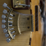 Drone strings: a small harp of 8 strings used in open tunings, with a movable bridge and a mechanical hand